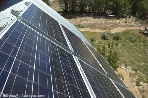 Photovoltaic panels mounted to a pitched metal roof on a straw bale house.